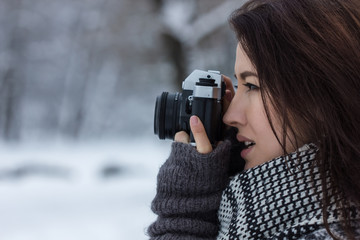 Girl looking through the old film camera in the winter park