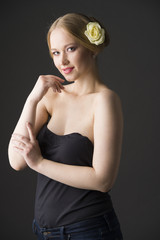 blonde with a yellow rose in her hair posing on a gray background