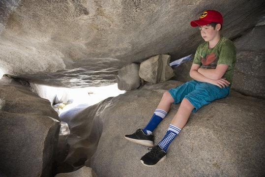 Pensive Caucasian boy sitting on rocks