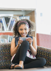 Smiling mixed race girl on sofa in library texting on cell phone