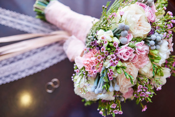 Beautiful bridal bouquet and engagement rings in blur, selective focus. Wedding bouquet and rings, copy space. Wedding concept