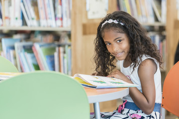 Smiling mixed race girl reading book in library
