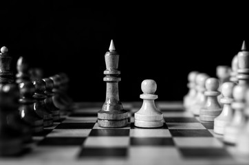King against pawn near full set of chess pieces. Business strategy concept