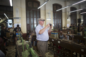 Man takes pictures during a visit at the H. Upmann cigar factory in Havana