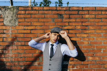 Fashionable man in cap at brick wall