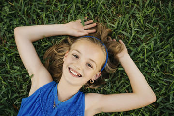 Close up portrait of smiling Caucasian girl laying on grass