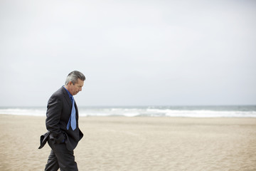 Pensive Hispanic businessman walking on beach