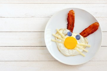 Easter breakfast with cute bunny face made of egg and bacon. On white plate against a white wood background.