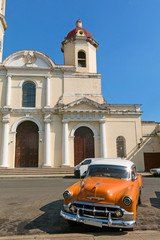 Old cars parked in the José Martí Park, in front of the Purisima Concepcion Cathedral. Cienfuegos, Cuba.