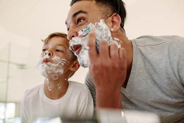 Funny father and son shaving in bathroom