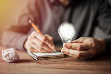 Businessman holding light bulb and writing down in the notebook new creative ideas. Concept of innovative technology and creativity.