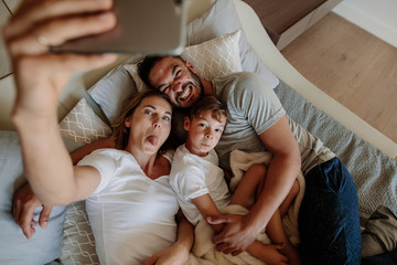 Crazy family on bed taking selfie