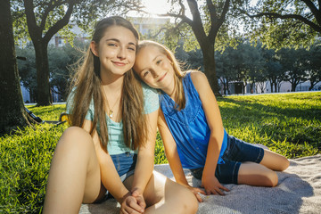 Portrait of smiling Caucasian girls on blanket in park