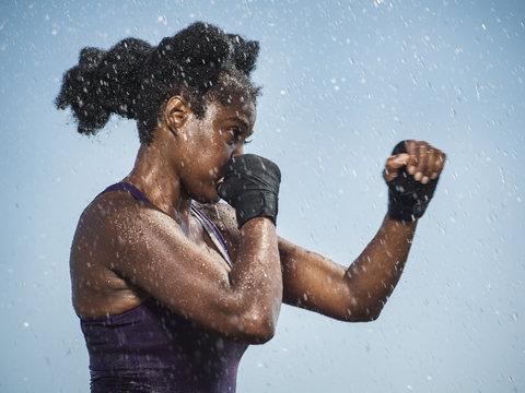 Water splashing on sparring Black woman