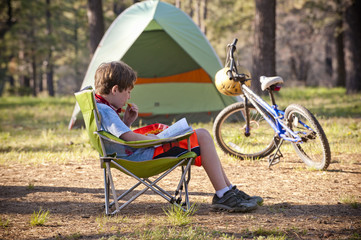 Caucasian boy reading book at campground