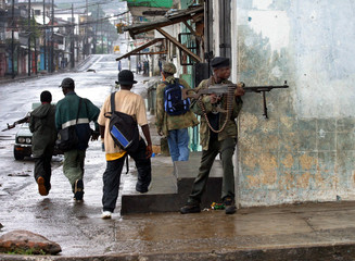 CHARLES TAYLOR'S FIGHTERS PATROL THE STREETS OF MONROVIA.