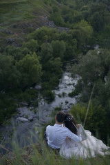 Caucasian bride and groom sitting on hill admiring river