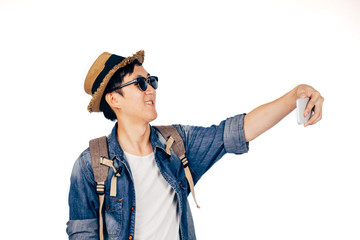 Young Asian tourist smiling and taking a selfie isolated over white background