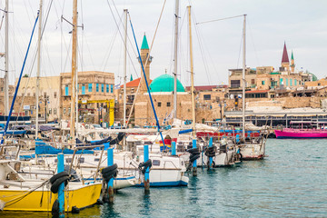 View on marina with yachts and ancient walls of harbor in Acre.