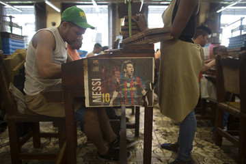A picture of Argentine soccer player Lionel Messi adorns a work station at the H. Upmann cigar factory in Havana