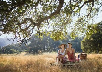 Portrait of smiling women relaxing on picnic blanket