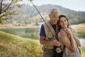 Couple with fishing rod hugging near river