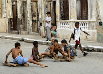 Children play with their toy sleds on a street in Havana