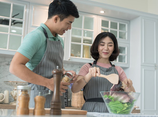 happy young couple have fun in modern kitchen indoor while preparing fresh fruits and vegetables food salad,Couple Cooking Hobby Lifestyle Concept,.Smiling young couple cooking food in the kitchen,