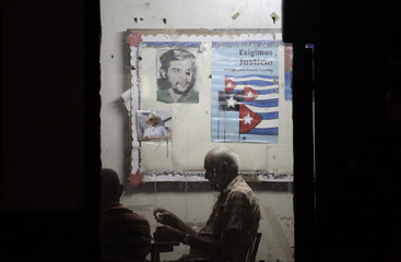 A man plays dominoes in an office of the neighbourhood CDR, beside posters of rebel leader Che Guevara and Cuban President Raul Castro, in Havana