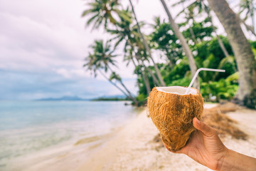 Fresh coconut water drink woman holding drinking on beach relaxation luxury holiday in Bora Bora, Tahiti, French Polynesia. Healthy natural refreshment on tropical vacation.