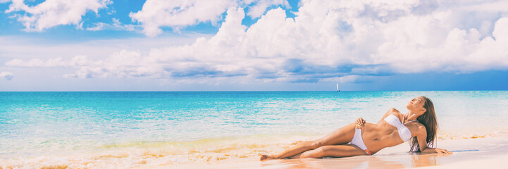 Beach paradise sexy bikini woman lying down on sand relaxing sun tanning in tropical caribbean travel destination for summer vacation. Panoramic banner landscape with copy space on blue ocean.