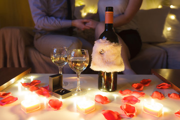 ​Couple in love on sofa celebrating engagement at home at night. Focus on the table with glasses of wine and gift.