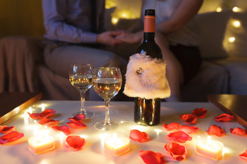 ​Couple in love on sofa celebrating Valentine's Day at home at night. Focus on the table with glasses of wine and gift.