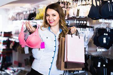 Female shopper boasting her purchases in underwear shop