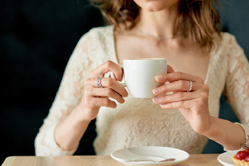 Young beautiful woman drinks morning coffee in cafe