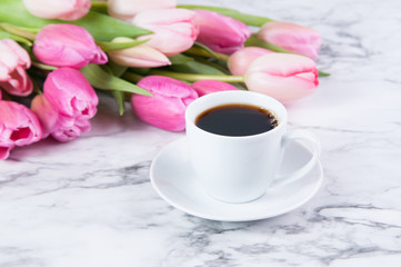 cup of coffee and pink tulips on a marble counter top