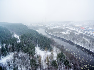 It is snowing in Vilnius, Lithuania, aerial top view of Neris river in winter