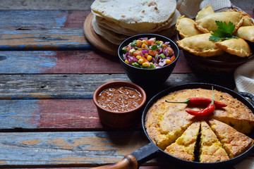 Mexican food mix - tacos, cornbread, salsa with tomato, red onion, lime, cilantro, corn and hot pepper sauce, empanadas. Copy space.