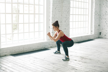 Picture of strong sporty girl wearing stylish tank top, sneakers and leggings doing squats on wooden floor at gym center against large windows background, having determined serious expression