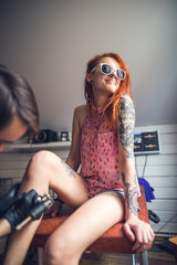 a tattoo artist makes a tattoo pretty girl with red hair. a tattoo on her leg.