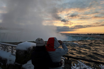 Visitors take pictures near the brink of the ice covered Horseshoe Falls in Niagara Falls