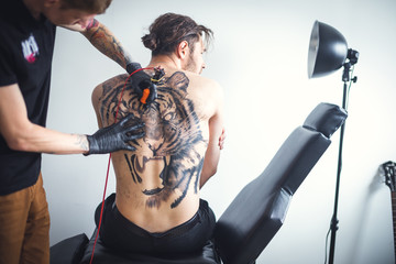Two men in a tattoo parlor. With the help of tattoo machines, the master does a tattoo on the back of a client