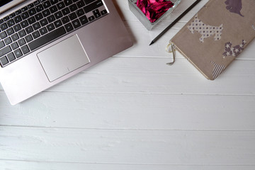 Laptop, notebook, pencil and decor on the white wooden desk. Business flat lay.