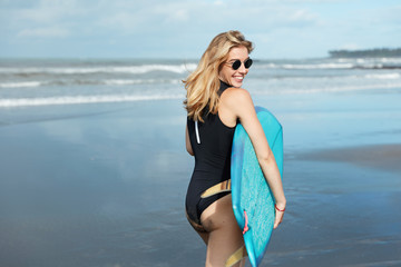 Outdoor view of blonde female surfer holds surfboard, dressed in swimwear, wears sunglasses, stands against beautiful seascape, has vacation at tropical country. People, summer and rest concept