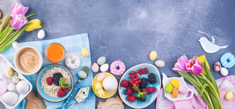 Delicious spring breakfast on a gray stone background. A bouquet of fresh tulips of pink and mint color. Small and large colored easter eggs. Oatmeal, biscuits, coffee, fresh raspberries and blackberr