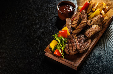 Foto op Plexiglas Vlees Assorted delicious grilled meat with vegetable. Mixed grilled bbq meat with vegetables. Mixed grilled meat on wooden platter