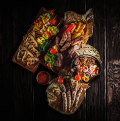 Assorted delicious grilled meat with vegetable. Grilled meat and vegetables on rustic wooden table. Top view.