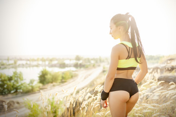 Young sports woman in black and green lingerie backside view on sunny day on the lake