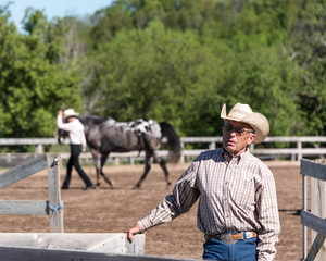 Older cowboy looking towards camera, other horse in distancd