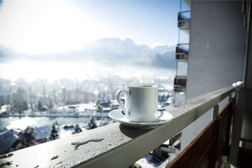 hot coffee on a handrail in a white mug surrounded by beautiful winter mountains